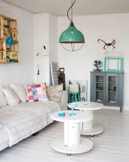 caixas de fruta na parede. bobines em madeira como mesas de apoio. candeeiro verde água. cores: branco + cinza + verde água