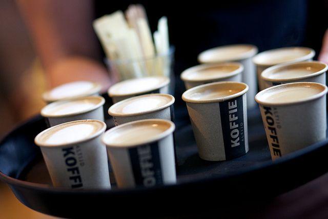 Een man zit in een café en drinkt koffie. Het meisje naast hem bestelt een koffie om mee te nemen, en twee 'uitgestelde koffie'. Wat is hier aan de hand?
