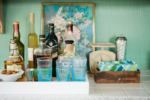 """Sneak Peek: Raya Carlisle """"I love bar carts, but our house doesn't have much wall space, and I don't know how it would go with small kids in the house. To get that feeling, Forest's whiskey and scotch bottles are on a counter in the kitchen. I put this together the other day with a West Elm tray, favorite glasses from Anthropologie and a milk glass bowl from my small collection."""" #sneakpeek"""