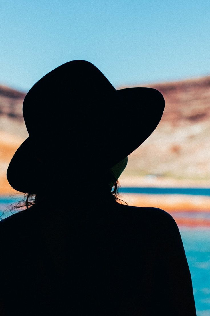 Silhouette of Woman Wearing Hat Near Sea during Daytime