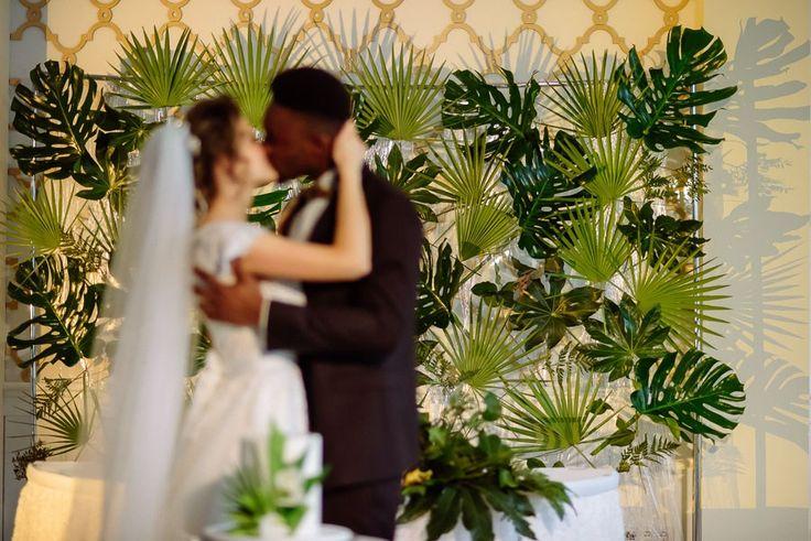 Поцелуй, люди в расфокусе. В резкости стена из пальмовых листьев.