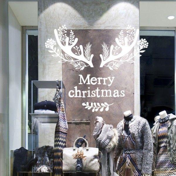"""Présentez vos voeux de façon originale avec cette décoration de vitrine de Noël. Composé de bois de cerf orné de branches, d'un texte """"Merry Christmas"""", et d'une branche de feuilles."""