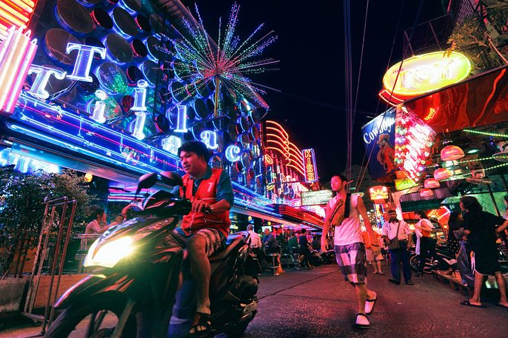 A Wretched Hive of Scum and Villainy   Soi Cowboy, one of Bangkok's infamous red-light districts, awash with alcohol and illegal gambling among its numerous go-go bars.  I was seated on the ground for nearly two hours waiting for the right moment to take this shot, between some parked motorcycles and a lineup of ladyboys, earning death stares from some passers-by and more than one thrown object.