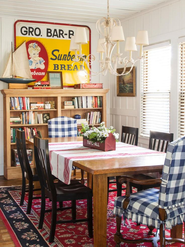 """By keeping most of the dining room as is—the table, side chairs, and Sunbeam sign were included in the sale of the house—Mary Kay could splurge on a metal chandelier from a Circa Lighting warehouse sale. """"Its size balances out the 9-foot ceilings,"""" she says. Updated with blue-and-white buffalo-check slipcovers, armchairs from a hotel furniture resale store could pass for brand-new."""