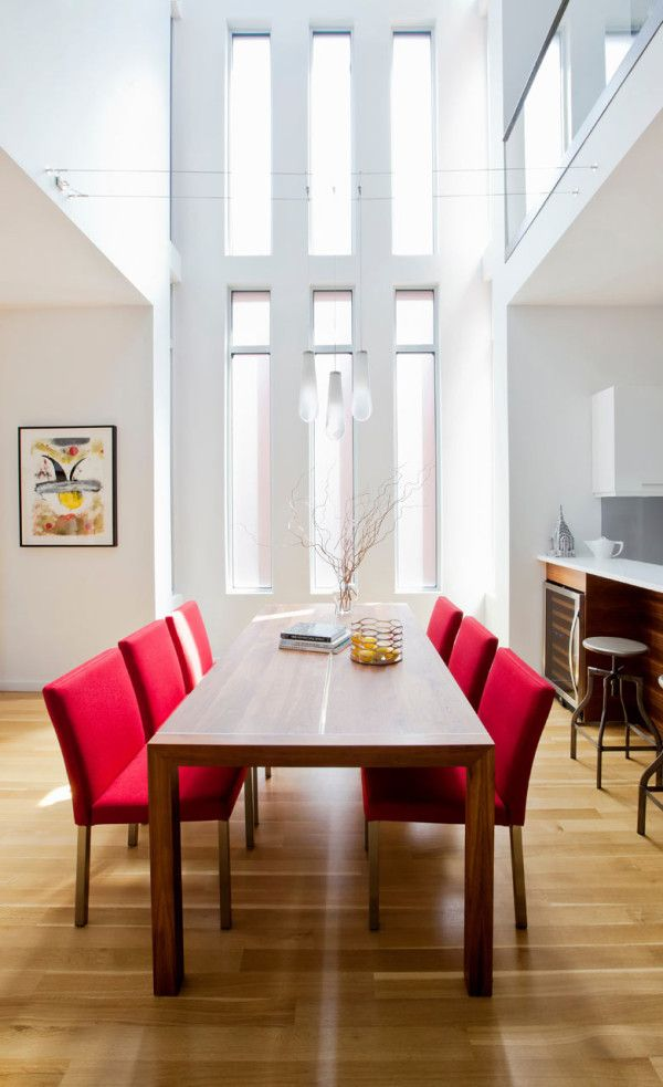 High ceilinged dining room with a pop of color from the red chairs.