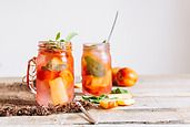 Cold cocktail with peaches and mint in handled jars