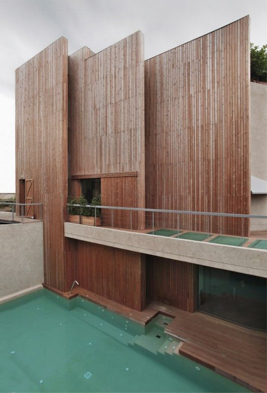 House Pedralbes / BCarquitectos. Offset vertical wooden clad walls + pool.