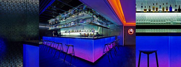 Barra de bar formada por vidrios de colores iluminados en parte oculta superior  y Silestone negro en parte superior de mostrador. Mueble de madera en DM en contrabarra forrados en chapa inox brillo y vidrios en laminados en colores según e iluminados en detalles circulares interiores.