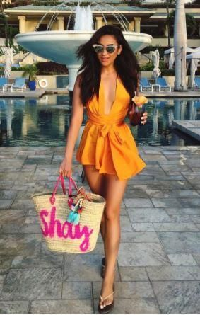 Shay is wearing an orange playsuit and a beach bag with this warm weather.