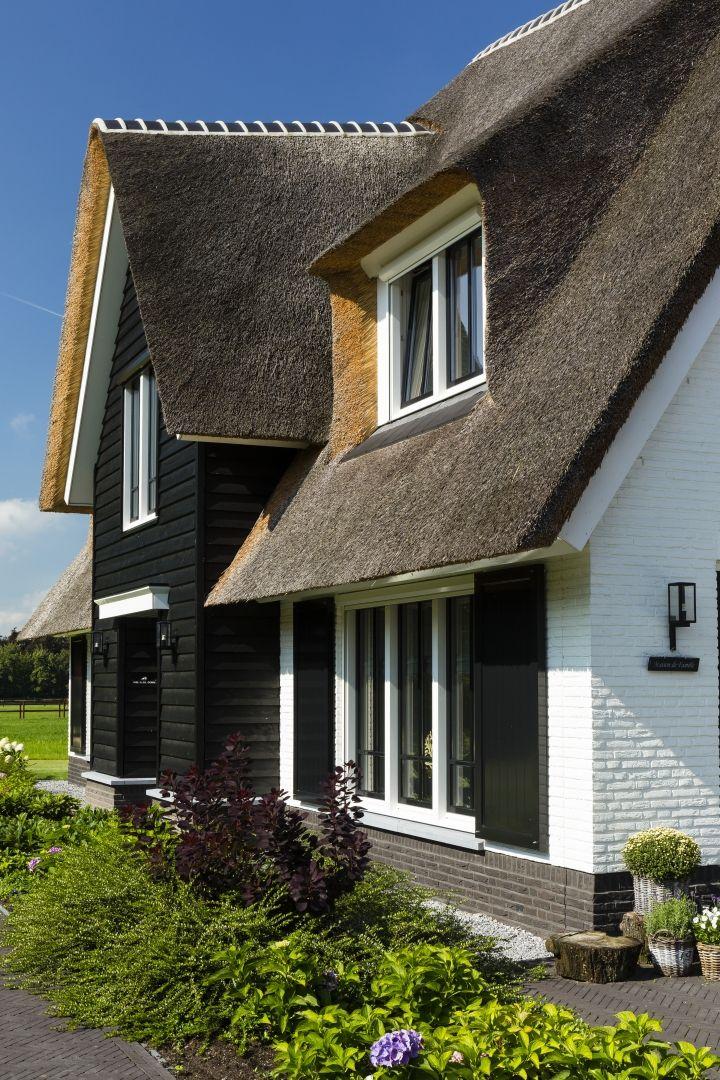 Landhuis detail voorgevel, contrasterende kleuren: witte muren, zwarte geveldelen en een rieten dak