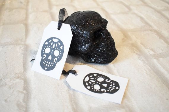 This listing is for a set of 2 gift tags featuring a skull embellishment.  The features of the tags are:  Die cut skull design in black card attached to a thicker white card for the main part of the tag. Size is 5cm x 8cm Comes with ribbon* for easy attachment to gifts Blank on the reverse for your own message  *The ribbon provided may be of a different finish to the one on the image but will be the same colour*  I'm a big fan of non traditional designs when it comes to cards and wrap - I…