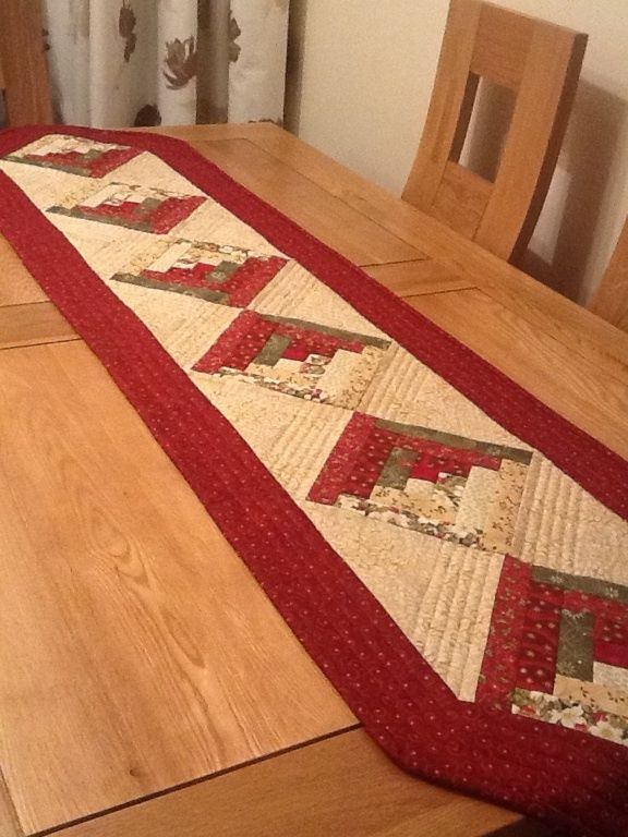 This is a Christmas log cabin table runner