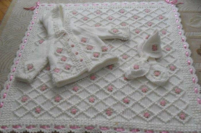 Küçük çiçekli pembe kurdelelerle süslenen yeni örgü bebek battaniye modeli