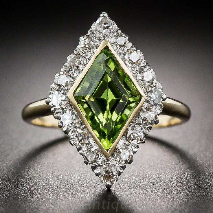 An unusual and exciting early-twentieth century treat starring a striking, electric lime-color peridot cut in a kite, or lozenge, shape. The enchanting gemstone fills a glittering frame of old mine-cut diamonds set in white gold. The peridot and ring shank are rendered in 14K yellow gold