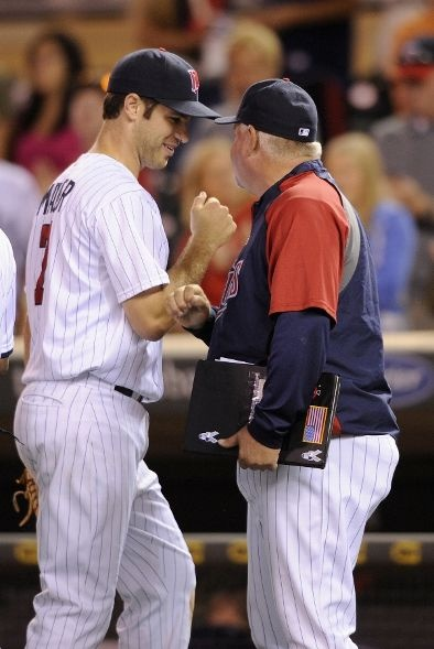 Joe Mauer #7 and Ron Gardenhire #35 of the Minnesota Twins celebrate a win against the Detroit Tigers on August 13, 2012 at Target Field in Minneapolis, Minnesota. The Twins defeated the Tigers 9-3.