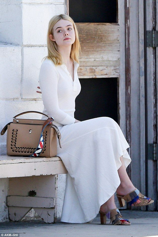 So chic: Elle Fanning looked elegant  when she was spotted wearing a simple white dress sitting outside the Gjusta Cafe in the boho neighbourhood of Venice in LA on Wednesday