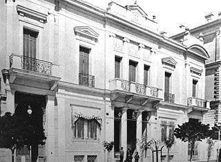 Το μέγαρο Αθηνογένους επί της οδού Σταδίου 50 οικοδομήθηκε μεταξύ των ετών 1875-1880, βάσει σχεδίων ξένου αρχιτέκτονα που εργαζόταν στην Ελλάδα (υπάρχει διχογνωμία εάν πρόκειται για τον Piat ή τον Eugene Trumb, ενώ σχέδιο κάτοψης έχει εντοπιστεί και στο αρχείο Ziller). Αξιοσημείωτη θεωρείται η  νεοκλασική σύνθεση με τις ιωνικές παραστάδες στην πρόσοψη, που συνδυάζεται με στοιχεία μπαρόκ. Στα τέλη του 19ου αιώνα στέγασε για ένα διάστημα την Οθωμανική Τράπεζα.