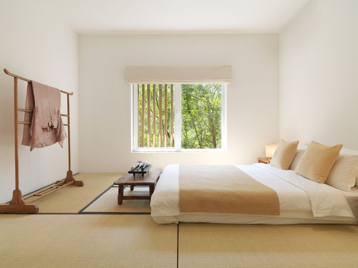 The house's six bedrooms have futons resting on tatami mats. In this one, a wooden kimono rack serves as sculpture and a place to drape clot...