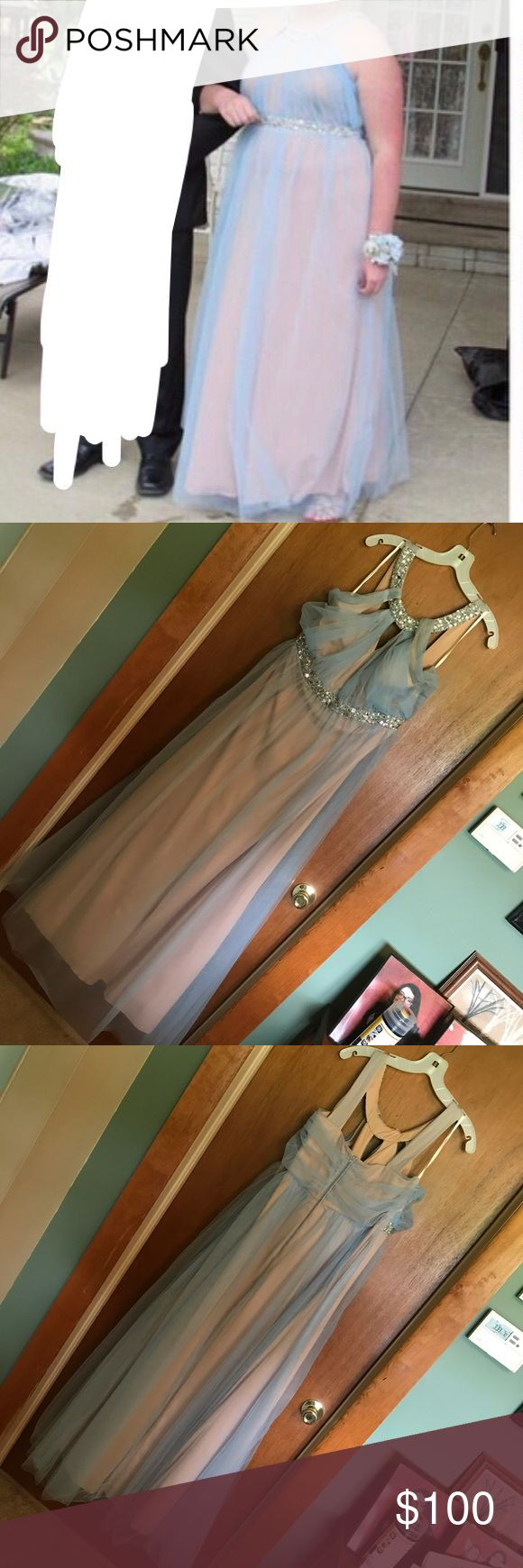 David's Bridal Formal Dress Blue/Nude Formal dress / prom gown from David's Bridal. It is nude underneath with a layer of light blue tulle over top. GREAT condition, nothing wrong with it, only worn once and kept in storage in a dress bag since then so it would stay in great condition. It zips up in the back. Size 17. Any questions feel free to ask. Originally $200. Price is negotiable, make an offer! David's Bridal Dresses Prom