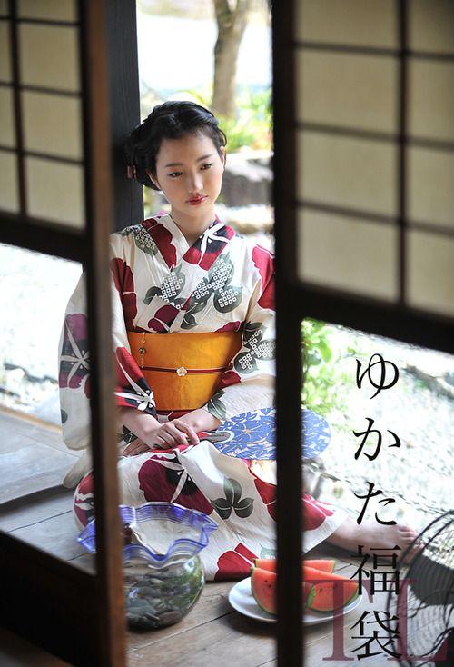 Yukata girl serving a typical summer fruit in Japan - watermelon.