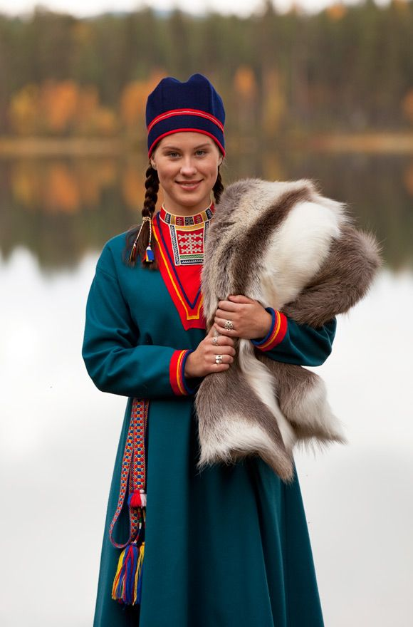 Lappland, Sweden. The young woman is wearing her Lule Sami kirtle. The neck section in red broad cloth is decorated with fine tin thread embroidery.