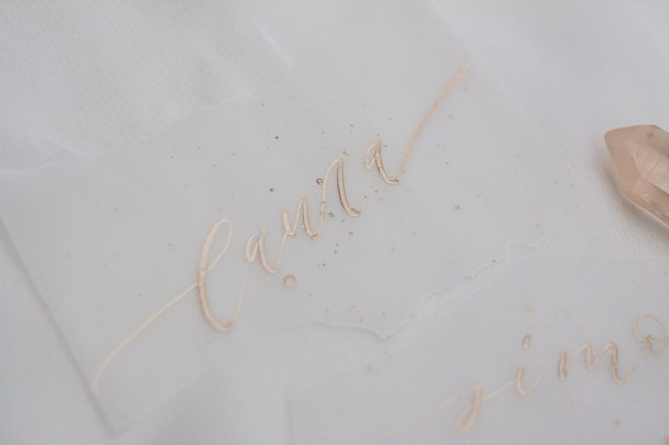 Ripped vellum place name with gold calligraphy and a modern gold splatter.