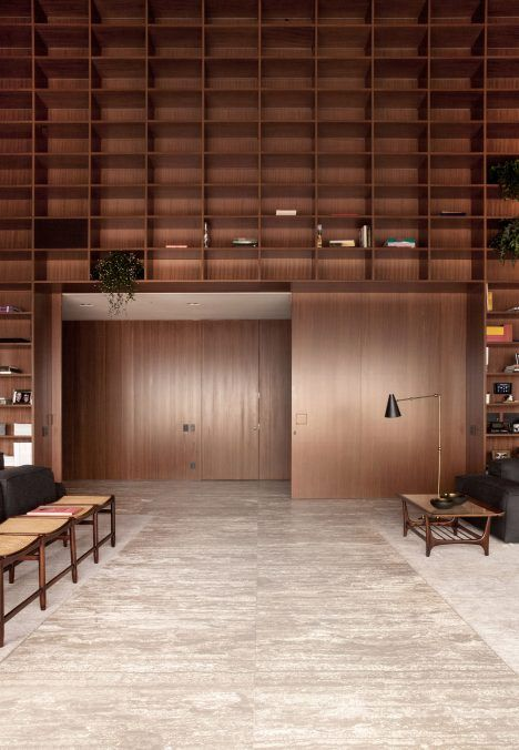 Floor-to-ceiling grids of wooden shelves cover double-height walls inside this luxurious apartment in São Paulo