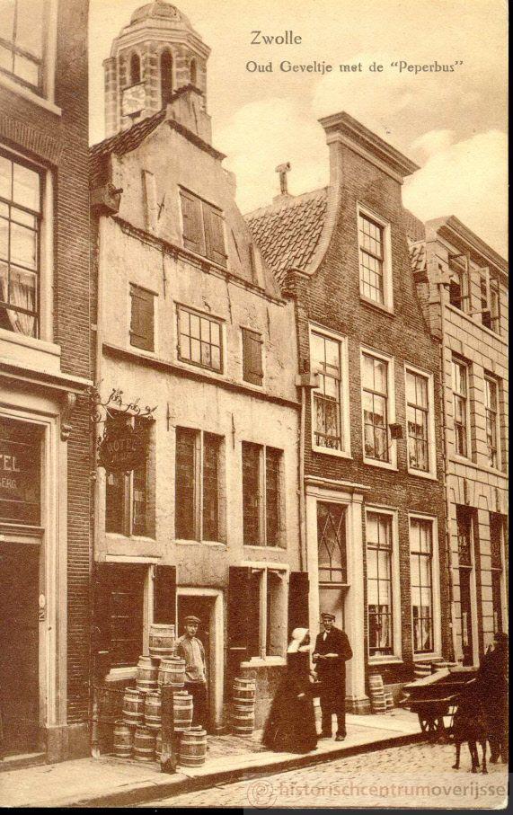 """Uiterst links Voorstraat 11, Hotel Meiberg; Voorstraat 13 kuiperij van familie Bekedam (1878-1914) met boerin in klederdracht en een handkar, op de eerste verdieping van Voorstraat 15 (bewoond door familie Bekedam) een spionnetje. In 1937 werden Voorstraat 13 en 15 samengevoegd door de cafehouder M.J.H. van Goor, die toen al enkele jaren een koffiehuis in Voorstraat 15 dreef. Vanaf 1963 vormden beiden huizen de """"Mercury-bar"""". kaart #Overijssel #Salland"""