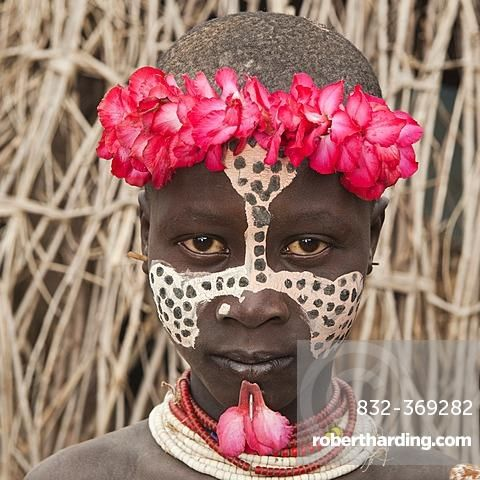 Karo girl with a floral headband, facial paintings, colorful necklaces and lip piercing, portrait, Omo river valley, Southern Ethiopia, Africa