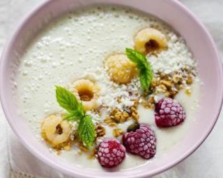 Smoothie bowl à la noix de coco, bananes, mûres blanches, framboises, menthe et granola