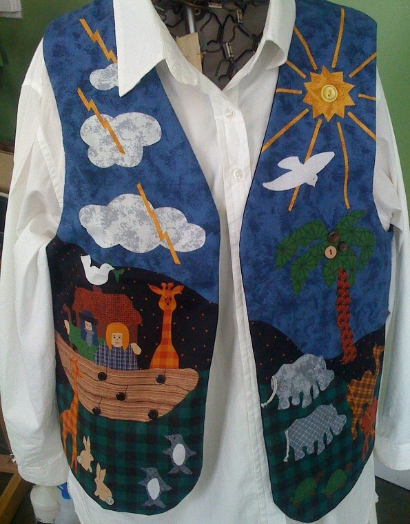 """A bright, colorful cotton blend fabric printed with images of Noah and his wife aboard the ark as some of the animals come two by two. Details enhanced with buttons, embroidery floss, and floppy ears. Lined in black cotton from a pattern marked """"Large"""" - 15"""" across tops of shoulders, 47 1/2"""" measured all the way around, just under the armholes, and 22 1/2"""" long from back of neck edge to bottom hem. This seems large, but considering it is going to worn over a shirt or sweater, it will be…"""