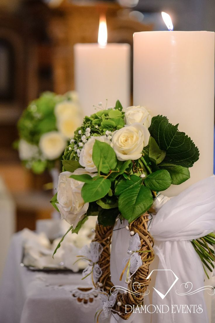 Wedding candles decorated with wooden garland and white roses.