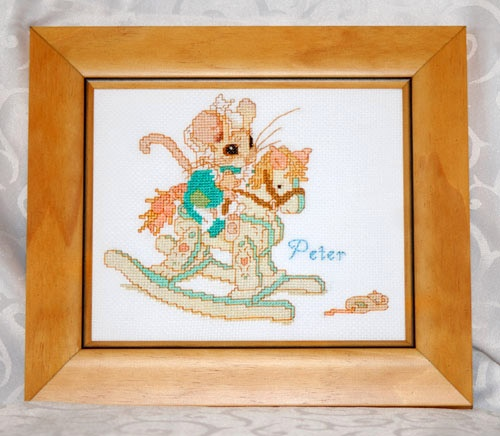 A beautiful framed cross-stitch embroidery depicting a darling little mouse playing on a rocking horse. On the floor lies the toy mouse he dropped. This charming picture will look aborable on the wall of a child's room. Personalise with the child's name. Ideal for a birthday gift or a special occasion.