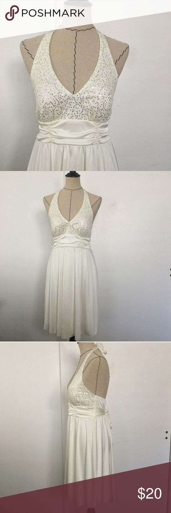 White cream sequin v neck halter dress 100% polyester. Adorable dress for that night out! V neck in the front with an open back. Sequins add the perfect touch to this Marilyn Monroe style dress. Ties in the back around neck. Length from top of sequins is approx 35.  Waist is approx 13.5. Ties in the back. BCX Dresses