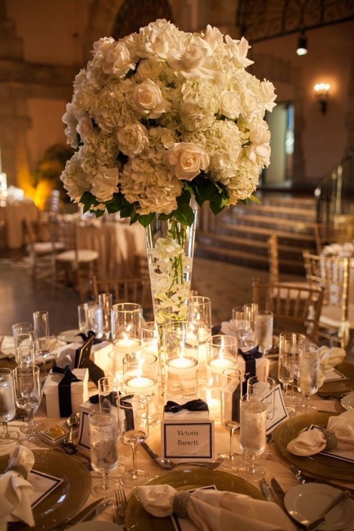 Tall centerpieces look great in venues with high ceilings for Glass tables for wedding reception