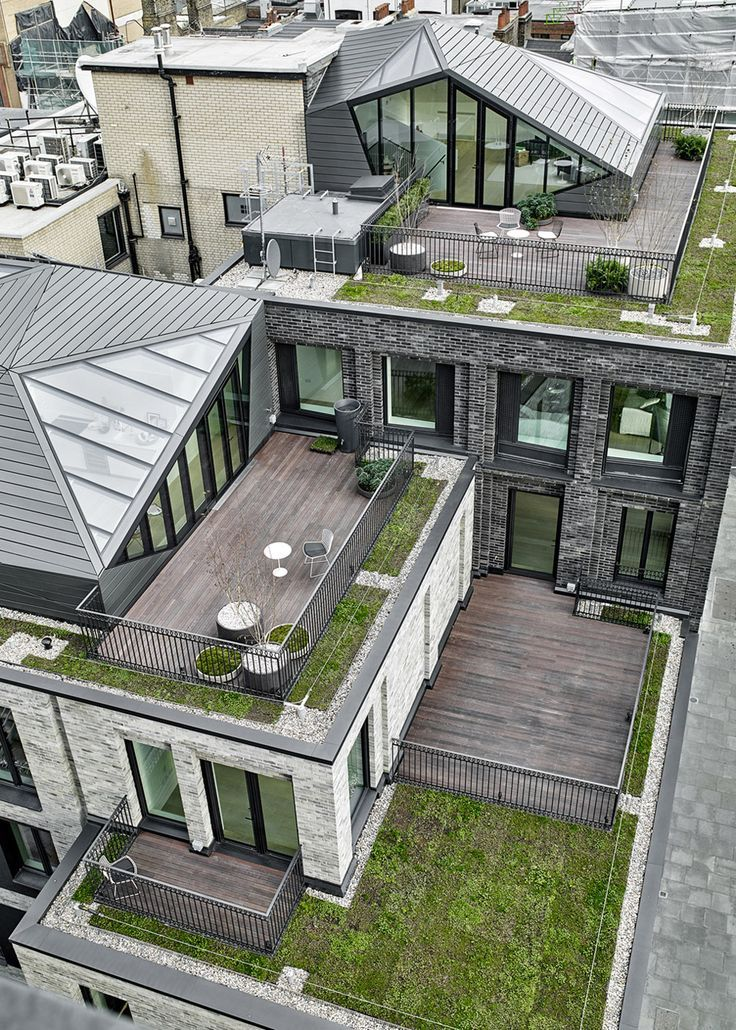 """The two top-floor residences have additional living space provided by so-called """"crystalline pavilions"""" – a pair of zinc-framed structures that adorn the rooftop, along with patios, decking and greenery."""