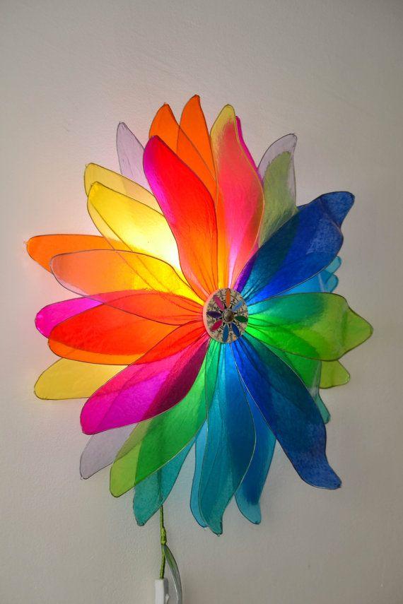 Un fiore luminoso che crea un mandala davvero suggestivo! Questa nostra lampada è formata da 32 petali di differenti gradazioni di colore, che con le loro trasparenze e sovrapposizioni creano unincantevole spettacolo per gli occhi e per lanima!  I petali sono interamente lavorati a mano uno per uno, con uno speciale procedimento attraverso lutilizzo di resine, diventano vetrificati ,e robusti, pur mantenendo la lampada leggerezza ed eleganza. Sono stati poi montati su un sostegno in legno…