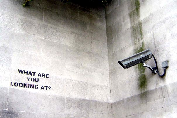 "It took a minute for me to realize that the camera is aimed at the wall and that Banksy (street artist) cleverly added the footnote.... ""What are you looking at?"".... Genius"