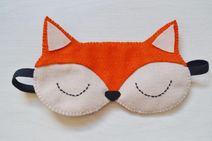 Máscara tapa olhos para dormir feita em feltro bege com detalhes em feltro laranja e preto, e bordado preto.