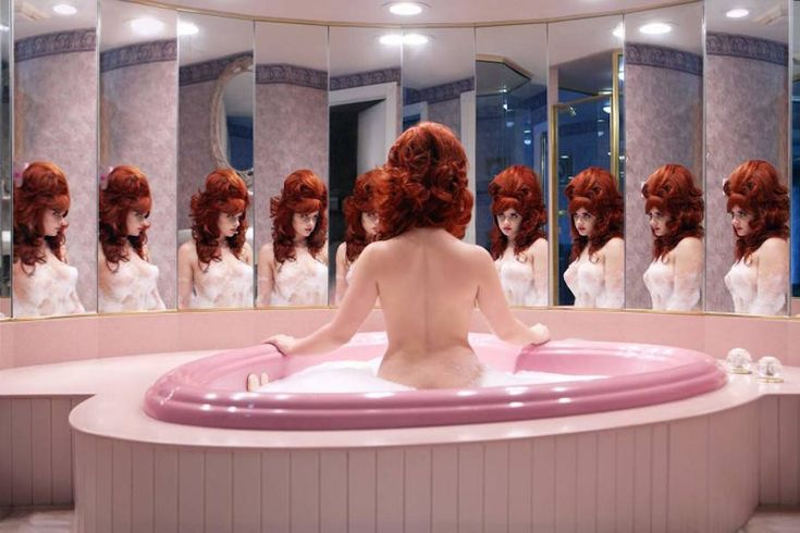 Unusual Retro Self-portraits  Juno Calypso is a photographer who depicts herself in the skin of a fictive character she imagined and called Joyce. She stages herself in honeymoons bedrooms pink kitsch bathrooms and retro-like interiors and highlights the feminine sensual and seductive side of her character through artifices beauty products and naked poses in front of multi mirrors. More you observe her settings more you perceive the loneliness of the character as the joyless atmosphere shes…