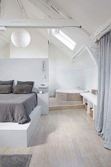 Très lumineuse, cette chambre parentale blanche dissimule dans le fond de la pièce une jolie baignoire d'angle octogonale.