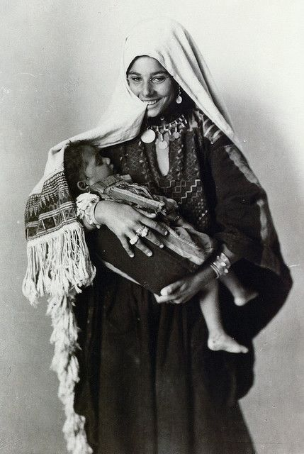 Palestine, 1920. A Palestinian Mother Smiling with her child in her arms.