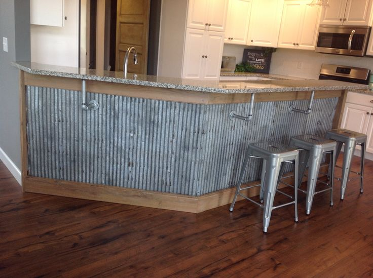 Reclaimed barn tin roofing used as wanescoting under a bar cabinet, with metal pipe corbals.