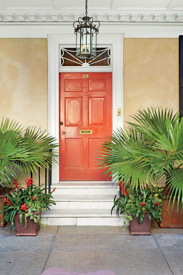 Solar Flair - Front Door Container Gardens That Will Impress Guests - Southernliving. The vibrant red and orange colors of a sunrise and sunset are artfully mimicked in this entryway container combo. Chinese fan palms, scarlet bromeliads, and gold-variegated acuba and ivy are incorporated in complementary earthenware planters.