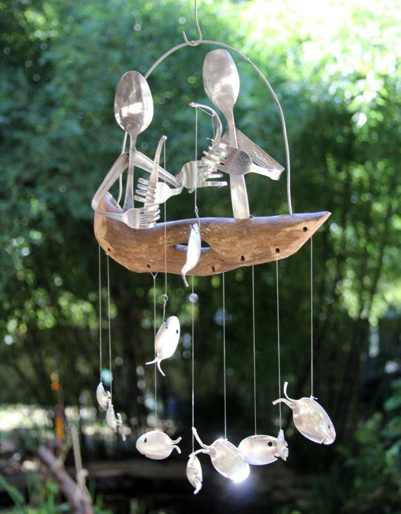 Delightful charming flat ware duo fishing atop a natural driftwood dingy a whimsical school of spoon fish swim playfully beneath     Wind chimes are