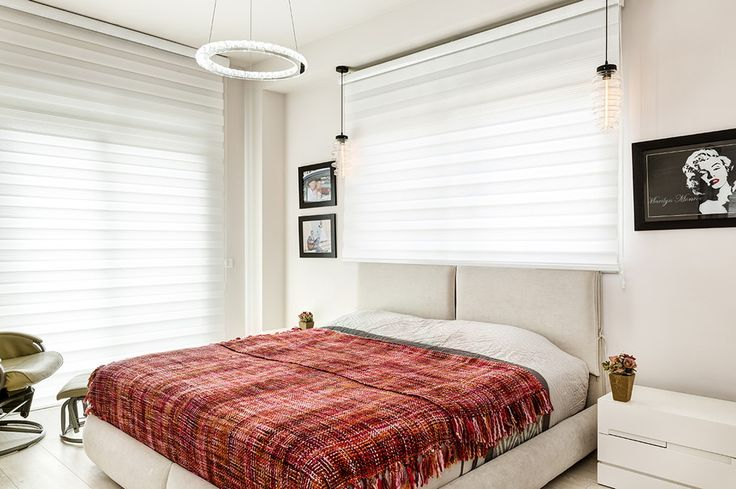 Massive windows covered with white blinds, unique round ceiling lamp and a comfy bed to through yourself on and just relax