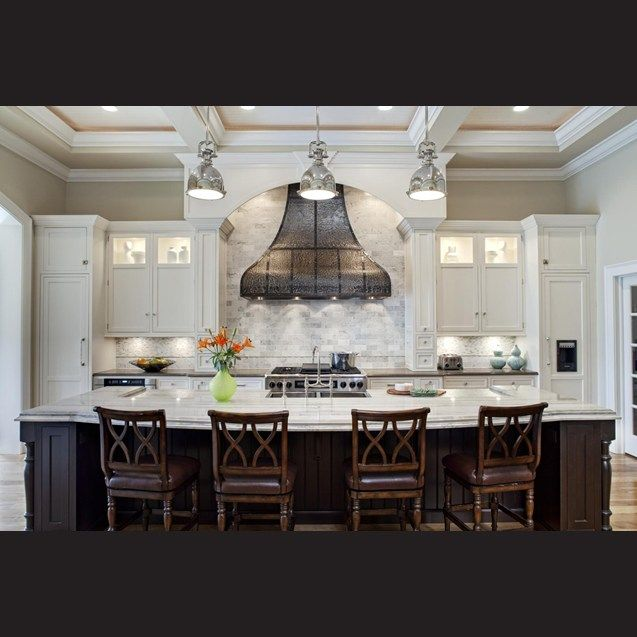 While the hood has an artisan, old-world look, this is balanced by elements such as the nickel lighting over the island. A sliver of metal above the perimeter granite countertop picks up on the material of the curvaceous feature.