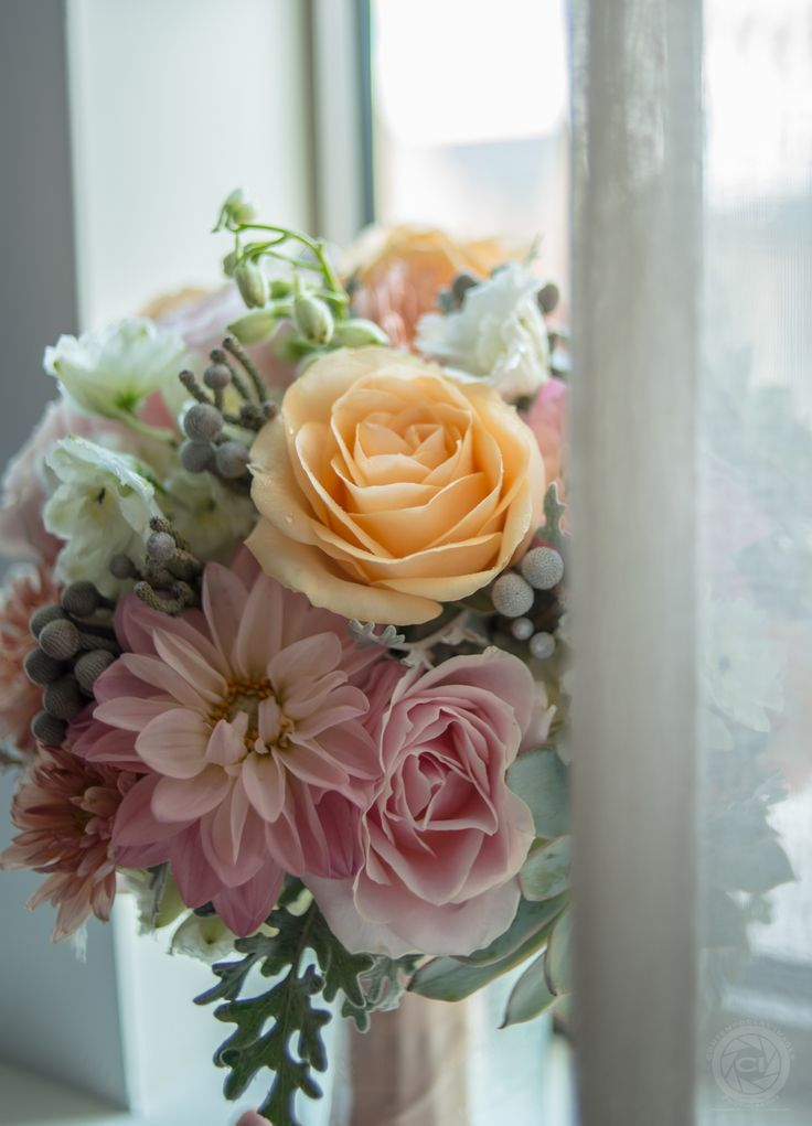 My beautiful wedding bouquet! Soft pink and orange roses, dusty blue succulents, brunia balls, pastel peach, coral, and pink mini dahlias, and a touch of white stock flowers and delphinium buds wired in. I loved my bright colored flowers, even in the month of November. Thank you Michael Angelos Events for creating this stunning wedding bouquet. http://www.michaelangelosevents.com