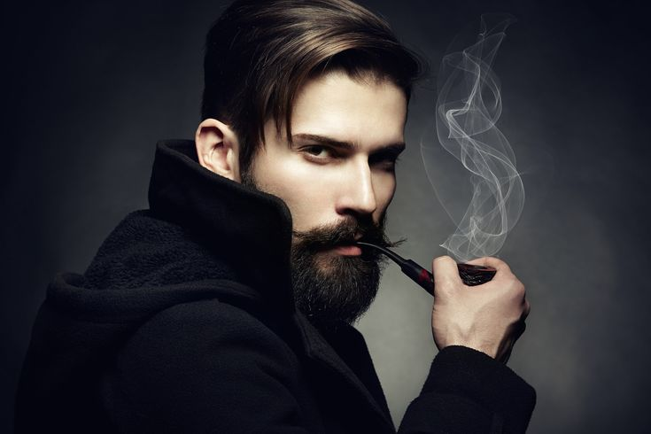 Artistic dark portrait of the young beautiful man. The young man - Artistic dark portrait of the young beautiful man. The young man smokes a tube. Close up