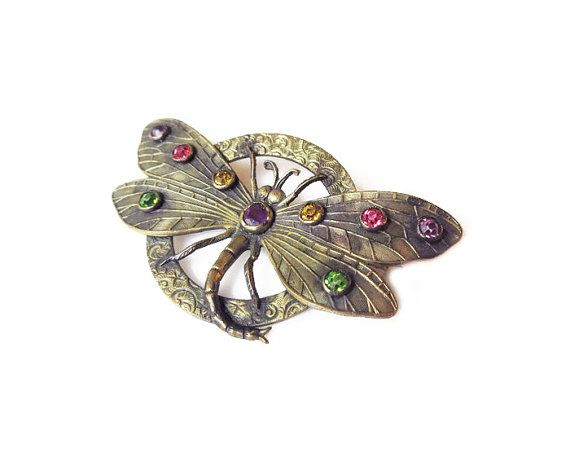 Victorian dragonfly brooch with paste rhinestones. This lovely piece features gold tone over brass metal adorned with pink, yellow, green and purple rhinestones. Age: estimated circa early 1900s Hallmarks: there is the number 7527 on the back, which I assume is a patent number. There are no other hallmarks. It looks Czech in origin based on construction and materials. Measurements: it is approximately 1-1/4 tall x 2-1/4 wide. Condition: it is in overall good condition, consistent w...